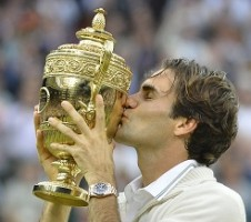 Roger Federer of Switzerland kisses the winners trophy after defeating Andy Murray of Britain in their men's final tennis match at the Wimbledon Tennis Championships in London